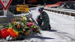 A miner lays flowers at the Pike River mine, where 29 miners died (29 November 2010)
