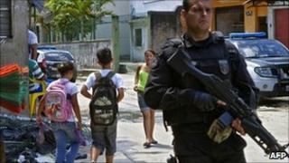 An armed policeman patrols the Complexo do Alemao shantytown in Rio de Janeiro as children walk past