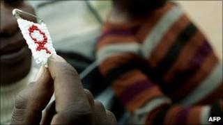 An HIV worker holding up a beaded Aids awareness badge in Botswana (Archive photo)