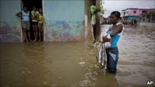 A young woman stands in a flooded street in Higuerote, Venezuela