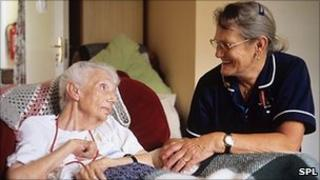 Smiling nurse talking to elderly patient