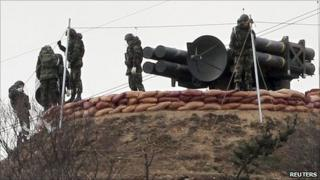 """South Korean marines stand beside the self-propelled surface to air missile system """"Cheonma"""" on Baengnyeong island near the western maritime border between the two Koreas, 3 December 2010"""