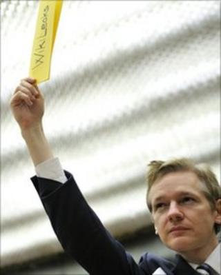 Julian Assange holds a piece of paper, saying Wikileaks