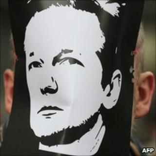 A demonstrator wears a mask depicting the face of Wikileaks founder, Julian Assange, during a protest over his arrest, outside the City of Westminster Magistrates' Court, London, 7 December 2010