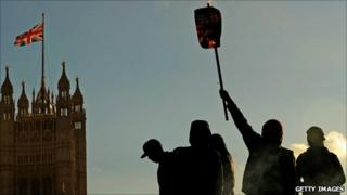 Protesters burn placards at an anti-tuition fees demonstration in London's Parliament Square