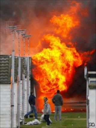 Prisoners collect their belongings as a blaze burns on 1 January.