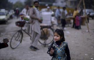 A Pakistani girl plays with a toy gun in Islamabad