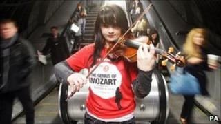 Olivia Shotton plays music by Mozart on her violin to commuters at Waterloo Underground Station