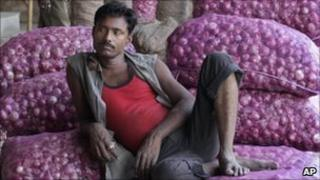 An Indian labourer sits on the sacks of onion at a market in Ahmedabad on 21 December 2010