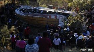 People stand around a bus after it plunged into a ravine near San Marcos in western Guatemala