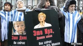 Activists hold portraits of journalist Irina Khalip and her son Danil outside Belarus embassy in Moscow, 27 Dec 10