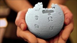 Hands holding the wikipedia symbol