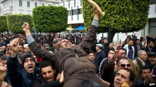 A Tunisian man holding a baguette is carried by fellow protesters during a demonstration in Tunis on 18 January 2011