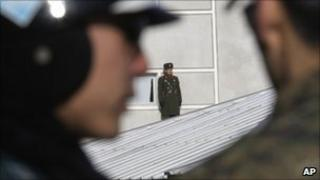 A North Korean soldier, centre watches southern soldiers at the border village of Panmunjom, 19/01