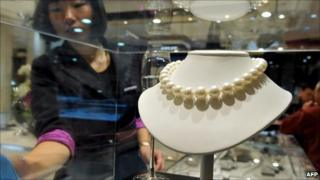 A worker checks a pearl necklace on display in Beijing.