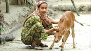 Woman in a village with a calf