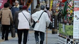 File image of two elderly women walking along a street in Tokyo on 21 December 2010