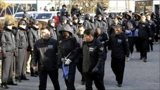 South Korean policemen lead Somali suspected pirates to the headquarters of the Namhae Maritime Police Agency in Busan, South Korea, 30 January 2011