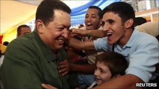 Venezuelan President Hugo Chavez greeting school children in a classroom on the 12th anniversary as president
