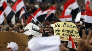 Protesters wave flags as they chant anti-government slogans during demonstrations against Egypt's president in Alexandria