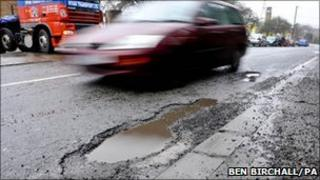 Car drives past pothole