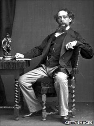 Charles Dickens sitting at desk