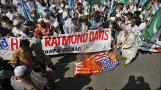 Supporters of the religious and political party Jamaat-e-Islami burn the US flag during a protest rally against American Raymond Davis in Karachi, 11 February 2011