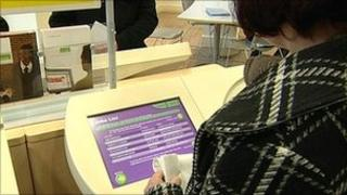 A woman looking at a database of job vacancies at a Job Centre Plus