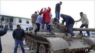 Residents stand on a tank inside a security forces compound in Libya