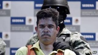 A soldier escorts Julian Zapata Espinoza, aka El Piolin, alleged member of the Los Zetas drug cartel