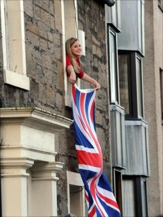 girl waves flag out window