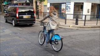 Woman riding a hire bike in London