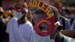 Revellers bearing anti-cholera messages perform during the National Carnival celebrations in Haiti