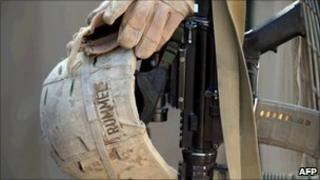 A US Marine's weapon, a helmet and a pair of gloves in Garmser, Helmand on 13 March 2011