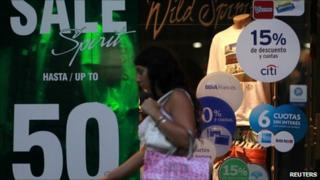 A woman walks past a shop with signs offering discounts in Buenos Aires. Photo: March 2011