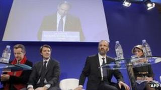 Participants in the debate on secularity listen to UMP leader Jean-Francois Cope (on screen) speaking in Paris, 5 April