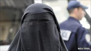 A woman in a veil outside a French police station