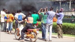 Residents take pictures of a bus burning during a demonstration in Ouagadougou on 16 April 2011