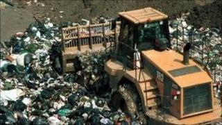 A tractor grinds over rubbish at a landfill