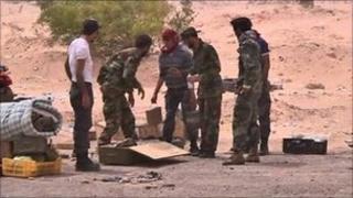 Libyan rebels unpack landmines before laying them near Ajdabiya, 17 April