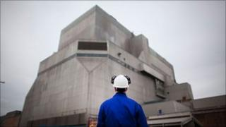 A workman in a hard hat looks up towards one of the buildings at Hinkley Point power station.