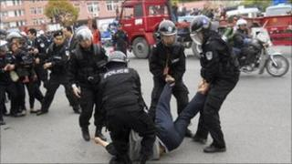 Police take away a truck driver and his wife at a protest near a port in Shanghai on 21 April 2011