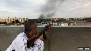 A rebel fires from a rooftop in Misrata, Libya (21 April 2011)