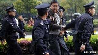 Policemen arrest a man after he threw rocks at a truck, as truck drivers continue with their third day of strike near a port area in Shanghai April 22, 2011.