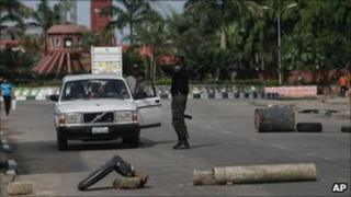 Policeman search a car at a road block during gubernatorial elections in Uyo, Nigeria, Tuesday, April 26, 2011.