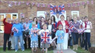 People in Lilac Drive, Monmouth, waving flags outside a house with bunting