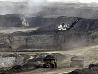 File photo: Mining trucks carry loads of oil laden sand after being loaded by huge shovels at the Albian Sands oils sands project in Ft. McMurray, Alberta, Canada