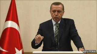 Turkey's Prime Minister Recep Tayyip Erdogan addresses the media as he stands by Turkey's national flag, 3 May 2011