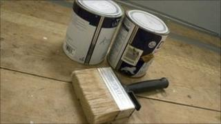 Paint tins and paint brush