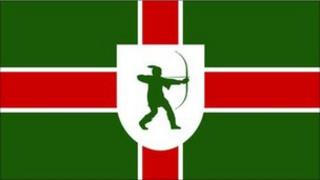 Nottinghamshire flag incorporating St George's cross on a green background, and a shield with the Robin Hood emblem in its centre